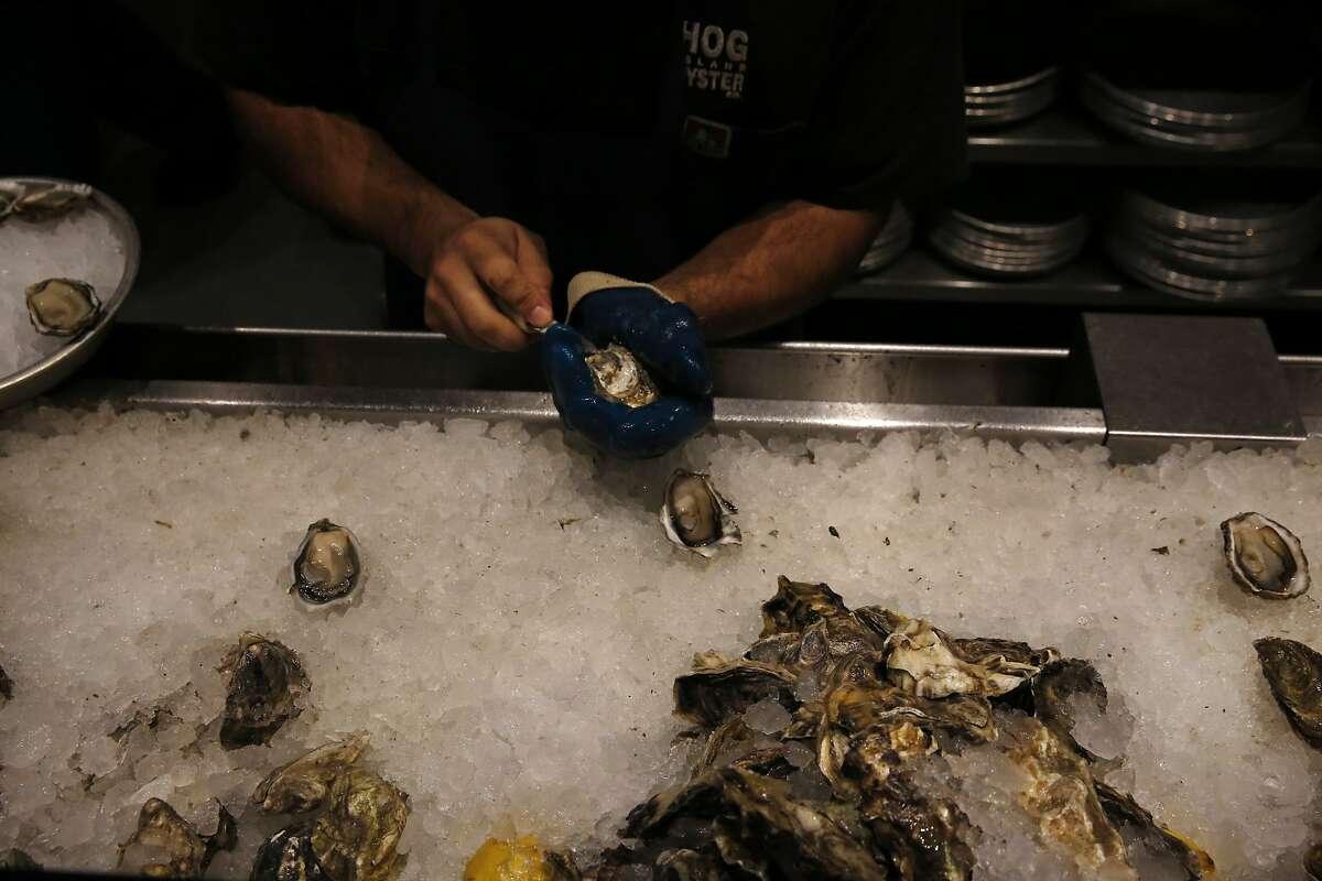 JosŽ Romo shucks oysters at Hog Island Oyster Co Inc in Oxbow Public Market Dec. 18, 2015 in Napa, Calif.