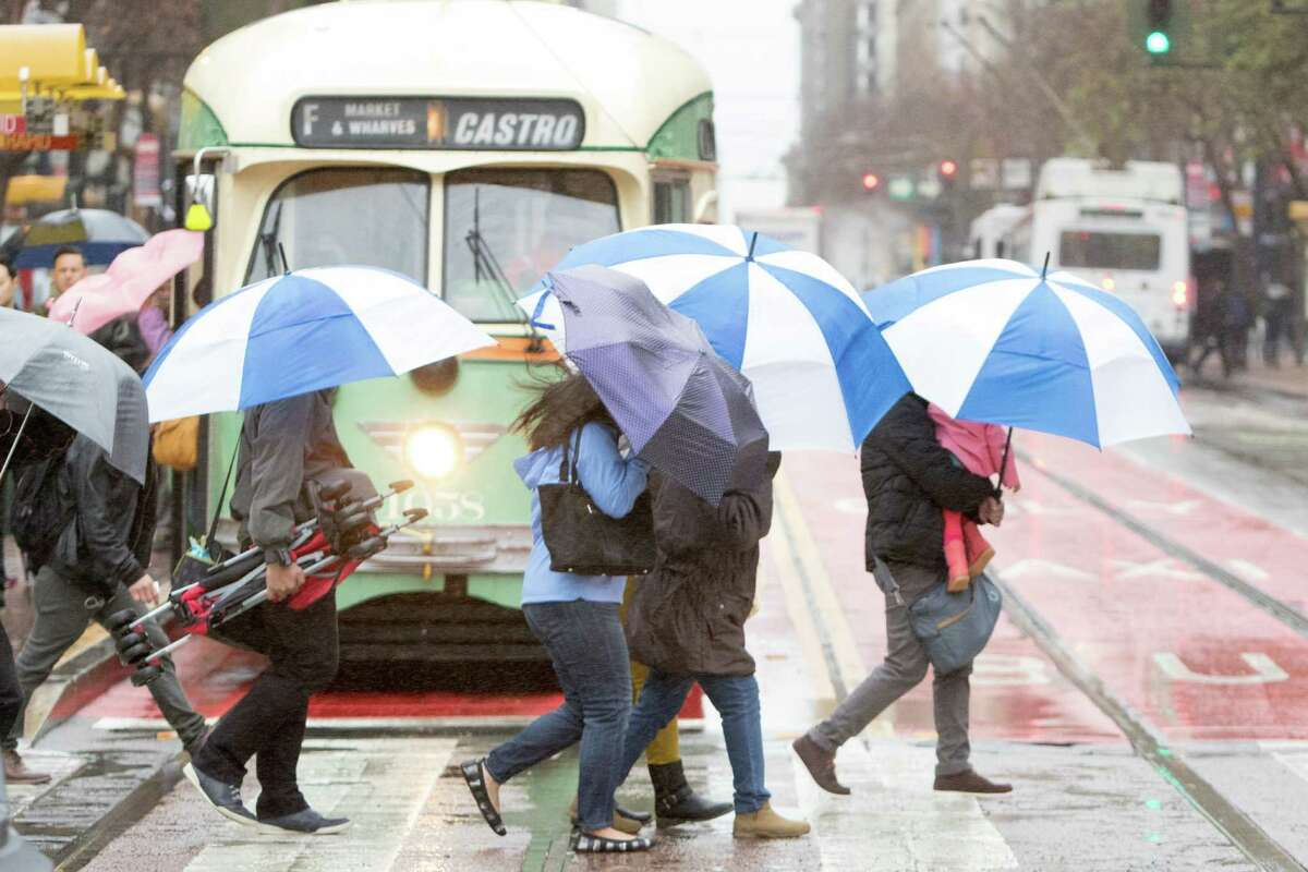 Pedestrians take cover during a light rainfall Monday morning in San Francisco.
