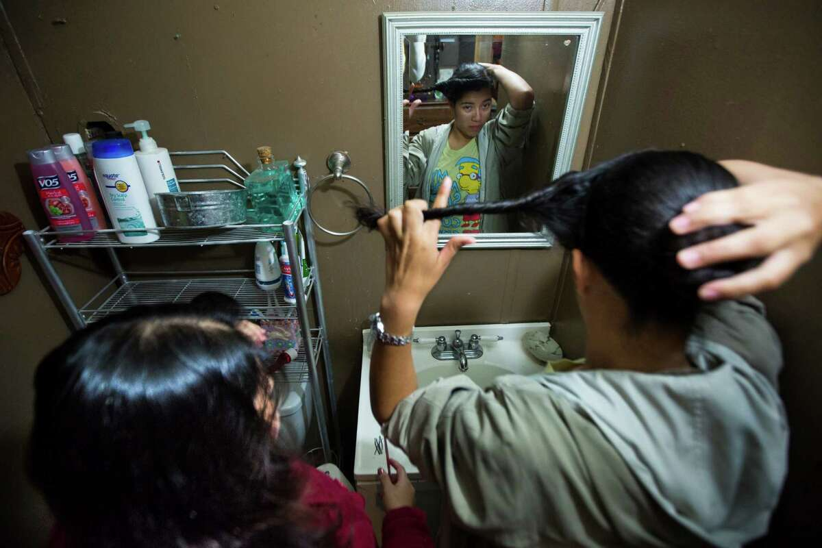 Erika Sosa, right, 17, and her older sister, Maria Sosa, left, 20, cram together inside the small bathroom of their two-bedroom trailer in Alvin, Thursday, Nov. 19, 2015.