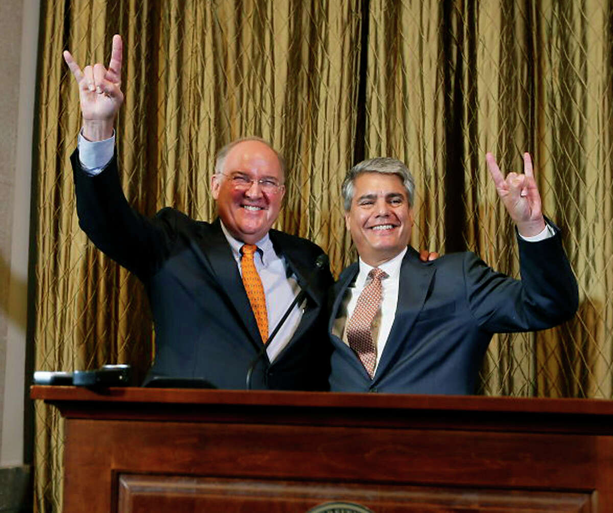 """Interim athletic director Michael Perrin and University of Texas President Gregory Fenves sign the """"hook em"""" during a press conference, Wednesday, Sept. 16, 2015, announcing Steve Patterson's replacement after his departure the day before, at the University of Texas, in Austin, Texas. (Ricardo Brazziell /Austin American-Statesman via AP) AUSTIN CHRONICLE OUT, COMMUNITY IMPACT OUT, INTERNET AND TV MUST CREDIT PHOTOGRAPHER AND STATESMAN.COM, MAGS OUT; MANDATORY CREDIT"""