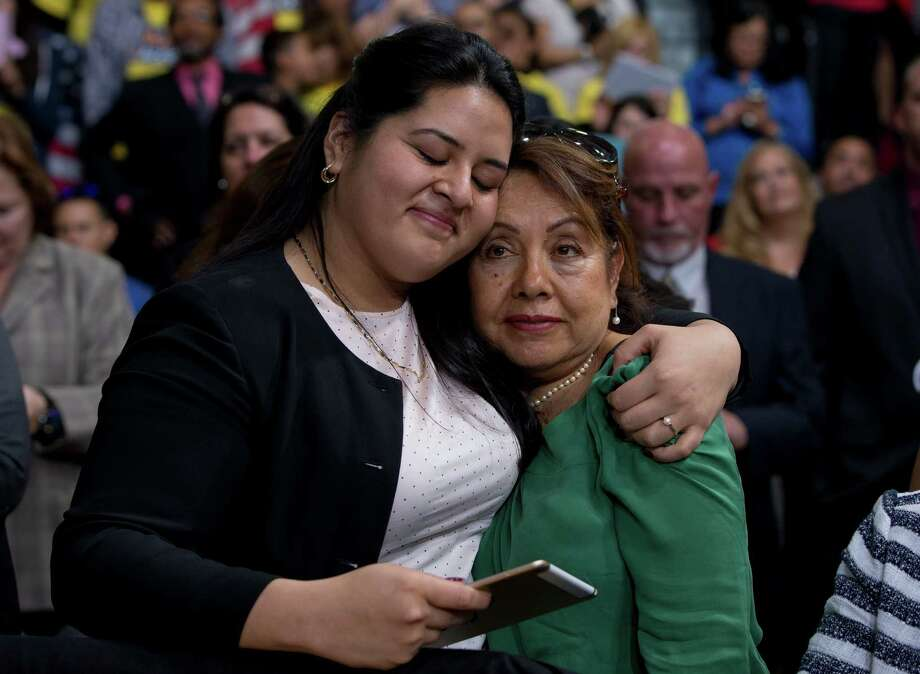 In this Nov. 21, 2014 file photo, Lorella Praeli, left, and her mother Chela Praeli, embrace as President Barack Obama speaks about immigration, at Del Sol High School in Las Vegas. The Hillary Clinton presidential campaign announced Wednesday, May 20, 2015 that Lorella Praeli has been named their Latino Outreach director. (AP Photo/Carolyn Kaster, File) Photo: Carolyn Kaster / Associated Press / AP