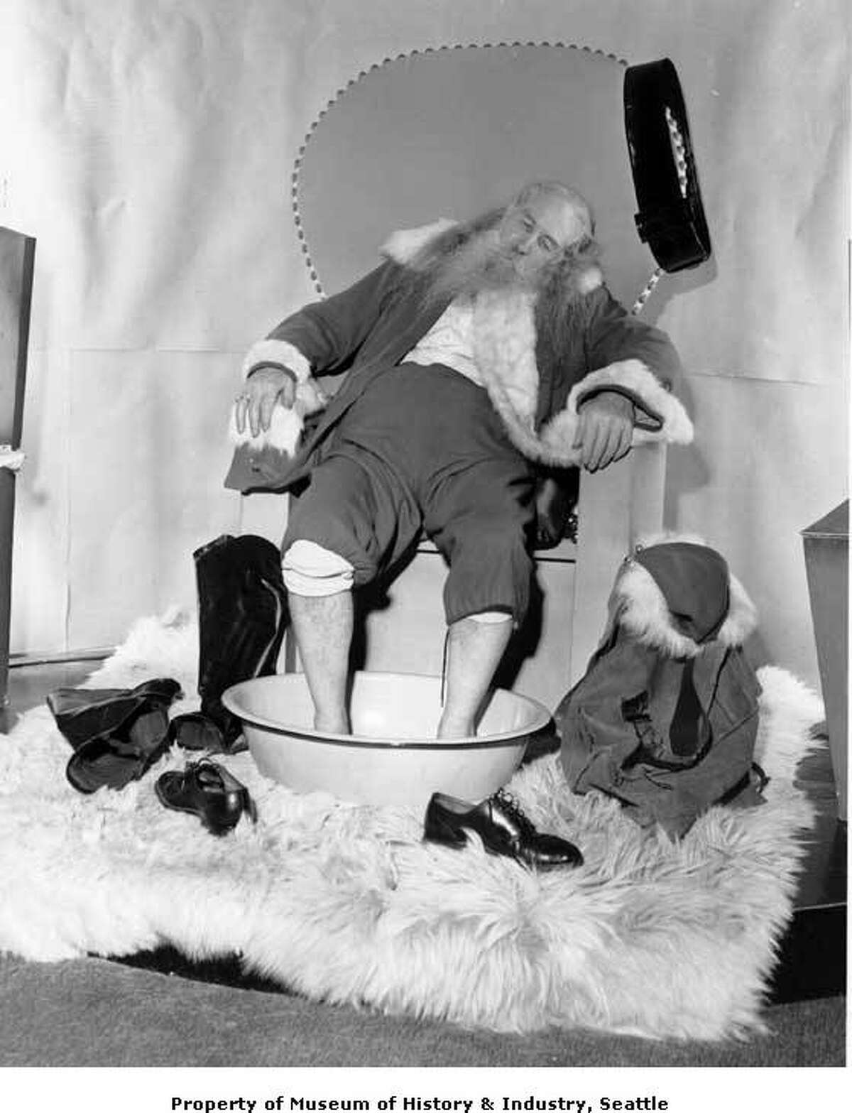 """""""On Christmas night in 1940, the Seattle Post-Intelligencer gave several accounts of Santa Claus' long day. The police reporter noted that Santa was """"unacountably missing"""" from the North Pole for twelve hours. A foreign correspondent reported that German anti-aircraft fire had wounded three of Santa's reindeer. The society editor noted that Santa had gotten home safely and was about to leave for a restful vacation. This December 1940 photo shows an exhausted Santa Claus bathing his tired feet in a hot mustard bath."""" -MOHAI. Photo courtesy MOHAI, Seattle Post-Intelligencer Collection, image number PI23234."""
