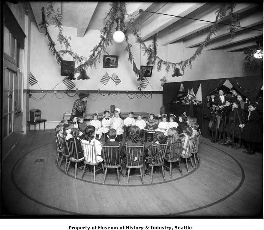 """""""For many years, Seattle's Bon Marche department store had children's activities at Christmastime. In this 1914 photo, a group of young children sits in a circle listening to a woman. At the right of the photograph, other children and women look on."""" -MOHAI. Photo courtesy MOHAI, PEMCO Webster and Stevens Collection, image number 1983.10.9180. Photo: Courtesy MOHAI"""