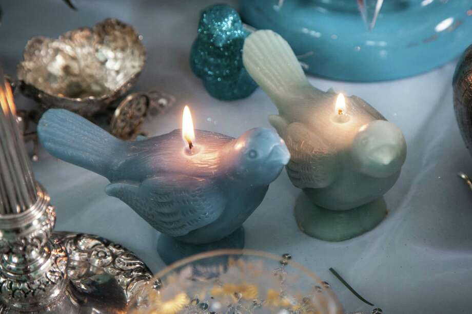 Small bird-shaped candles in shades of blue were tucked into the table setting. Photo: Sam Roberts /For The Express-News