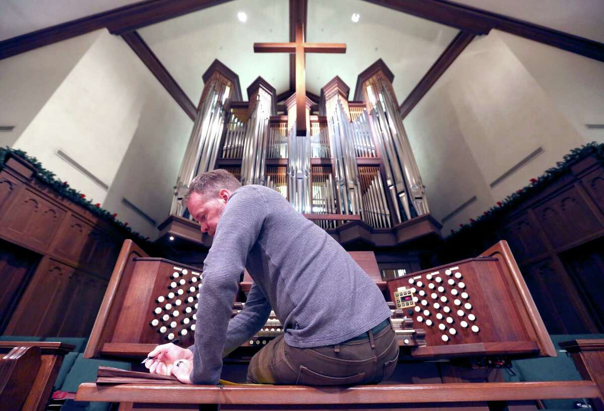Curtis Bobsin, owner of C. Bobsin Organs, takes extensive notes -- to even include the temperature in the sanctuary -- as he tunes the pipe organ Wednesday Dec. 16, 2015 at Laurel Heights Methodist Church.