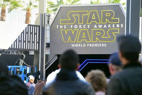 "(FILES) This December 14, 2015 file photo shows people as they watch from behind police barricades and closure of streets in Hollywood, California as preparations take place for the premiere of the latest Star Wars film, ""The Force Awakens"". Disney jumped in opening trade December 21, 2015 on record-setting sales of its new ""Star Wars"" blockbuster as US stocks climbed in the first session of a holiday-shortened week.Five minutes into trade, the Dow Jones Industrial Average was at 17,261.54, up 132.99 points (0.78 percent). AFP PHOTO / FREDERIC J. BROWN FREDERIC J. BROWN/AFP/Getty Images"