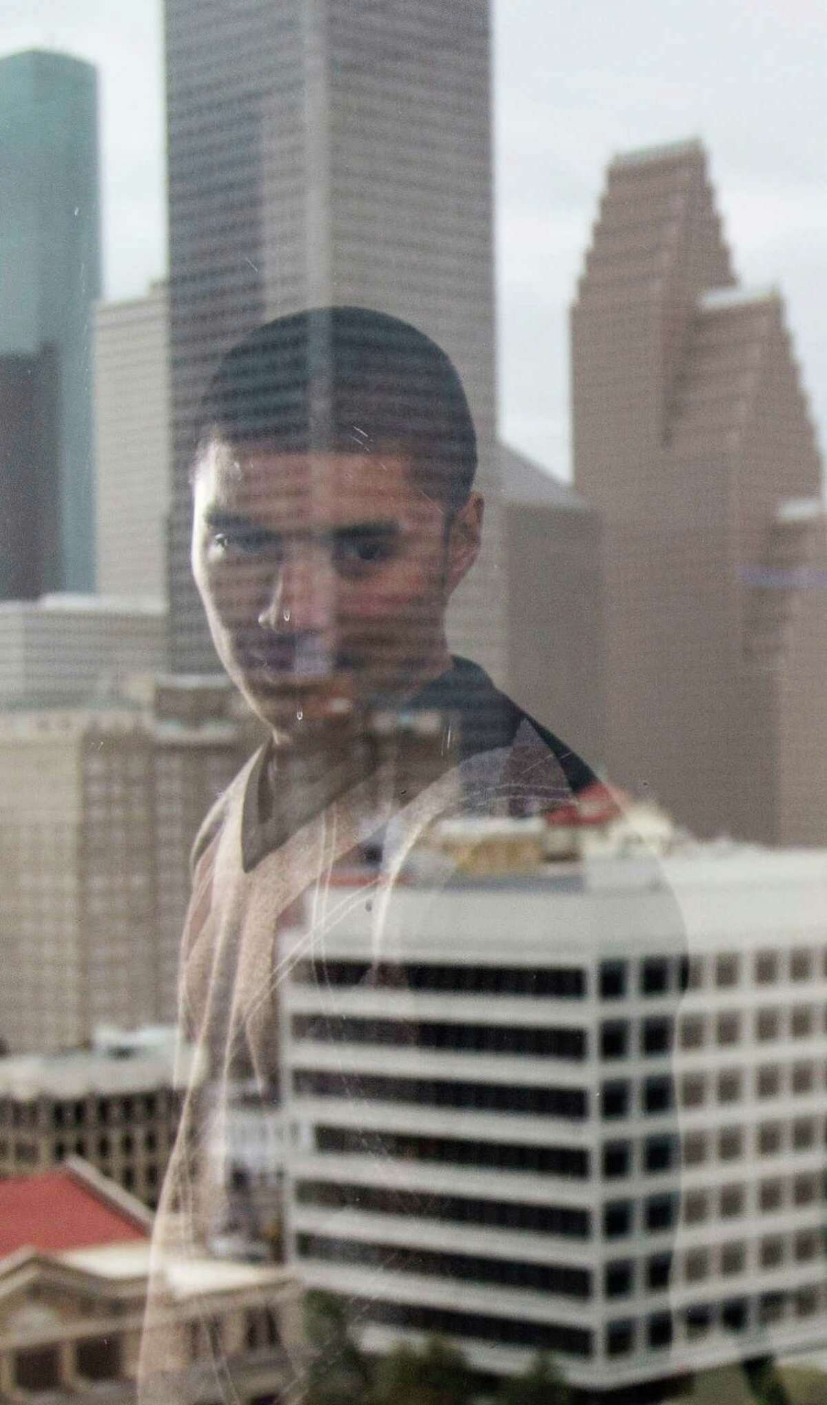 Joseph Salazar is reflected in a window at the Public Defender's Office Monday, Oct. 26, 2015, in downtown Houston.Salazar was accused of trying to disarm a peace officer at the Harris County Jail last July. His court-appointed public defender was able to get his case dismissed after he subpoenaed jailhouse video showing the incident.