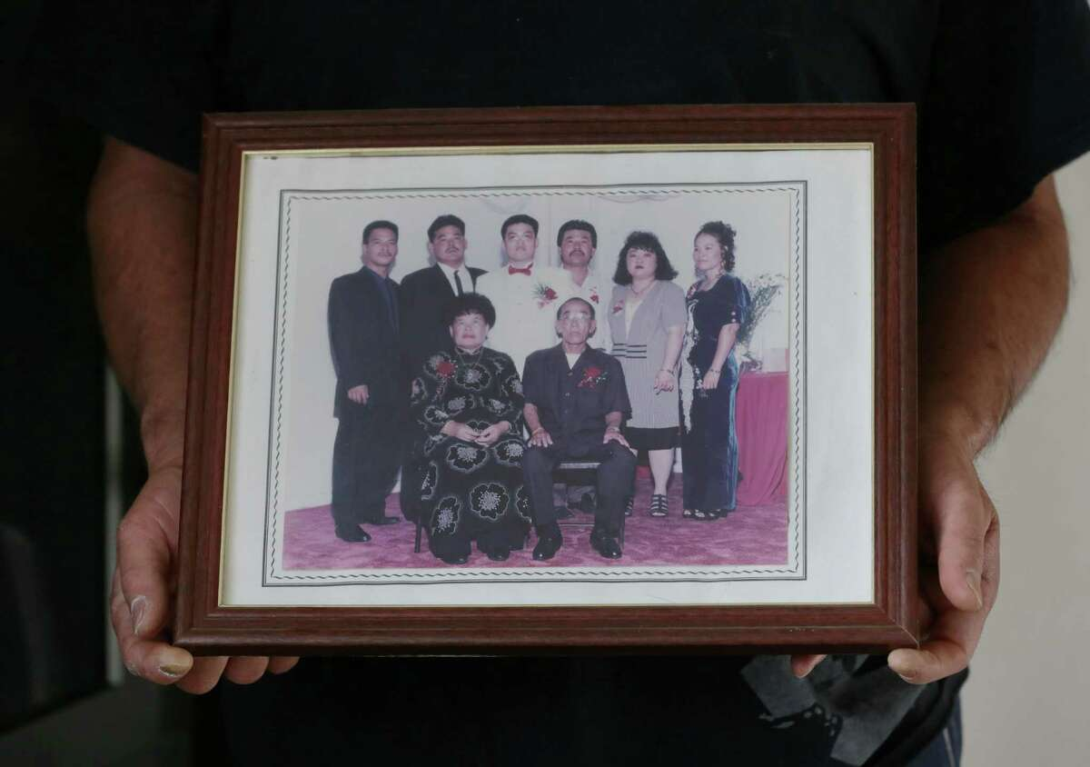 Hoang Nguyen, son of 83-year-old Tung Nguyen, poses for a portrait with a family photo Wednesday, Dec. 9, 2015, in Houston. After four months in the Harris County jail, Nguyen's father Tung died in June 2009 from MRSA pneumonia.