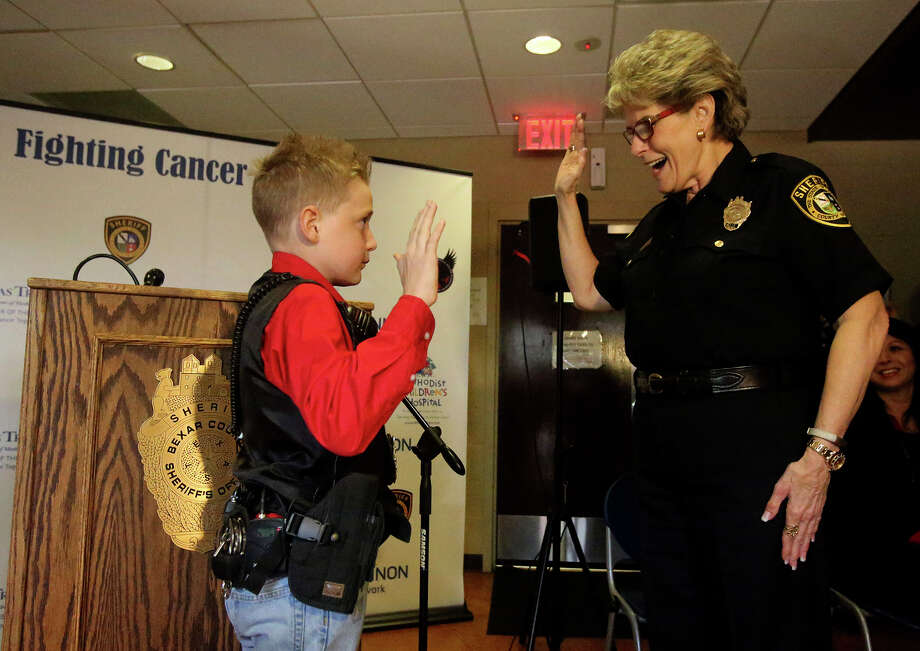Bexar County Sheriff Susan Pamerleau (right) swears in 11-year-old Colton Harvell (left) Monday December 21, 2015 as a deputy for a day during a ceremony at which he met his bone marrow donor. Harvell was diagnosed with leukemia in 2012 and did not respond to chemotherapy so doctors determined that his best chance for recovery was a bone marrow transplant. A search was made through an international registry and a match was found with 34-year-old Alex Hartman in Germany. Harvell had a chance to meet Hartman at the ceremony. Photo: John Davenport, Staff / San Antonio Express-News / ©San Antonio Express-News/John Davenport