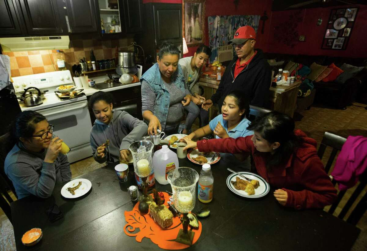 Dulce Sosa, 15, from left, with her sister Rocio, 12; mother Leticia Sosa; sister Erika, 17; father Jose Sosa; sister Lupita, 8; and sister Maria, 20, gather around the table in their two-bedroom trailer in Alvin.
