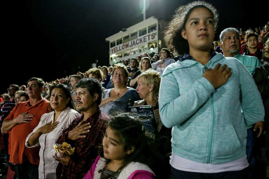 Leticia Sosa, second from left, her husband Jose and their daughters Lupita, 8, and Rocio, 12, put their hands over their hearts as the national anthem is played at an Alvin High School football game. The two girls are American citizens. Photo: Michael Ciaglo, Staff / © 2015 Houston Chronicle
