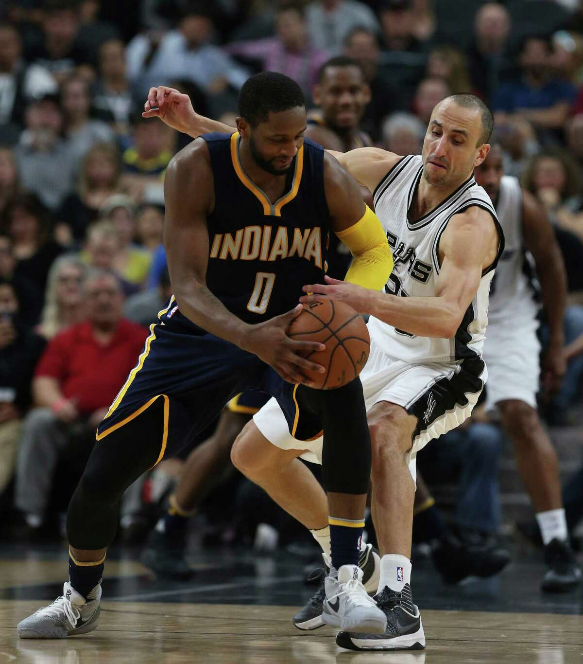 Spurs' Manu Ginobili attempts a steal from Indiana Pacers' C.J. Miles during the second half at the AT&T Center on Dec. 21, 2015. The Spurs won, 106-92.