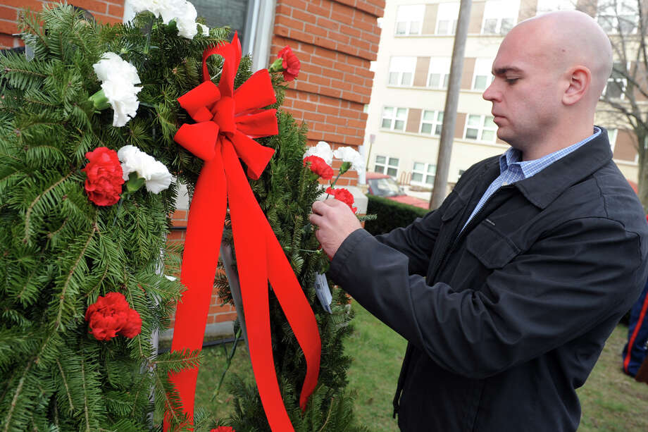Ross Shutak, a member of the Pivot Ministries Choir, places a carnation in a wreath honoring those who have passed away during the 11th Annual Community Homeless Person's Memorial held at Homes for the Brave in Bridgeport. Photo: Ned Gerard / Hearst Connecticut Media / Connecticut Post
