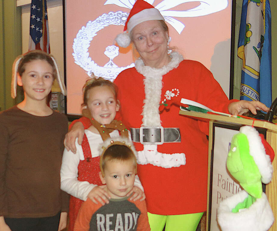 """Fairfield Children's Librarian Cindy Barich, outfitted as the Grinch, wth Grace Bartlett, 8, who portrays Max the Dog; Samantha Petriprin, 8, as Cindy Lou Who; and Jake Petriprin, 3, as a reindeer, at the dramatic reading of """"How the Grinch Stole Christmas"""" at the Fairfield Public Library. Photo: Mike Lauterborn / For Hearst Connecticut Media / Fairfield Citizen"""