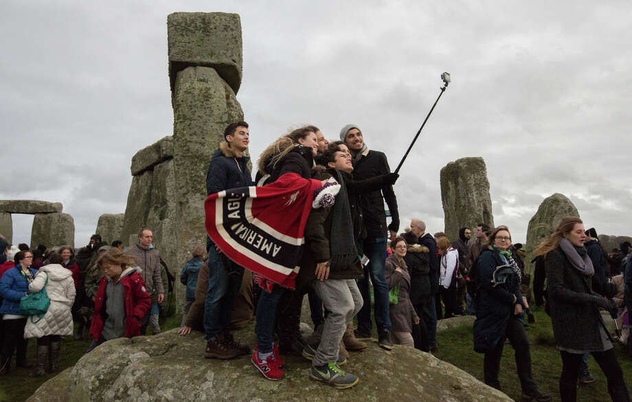 People gather to take a selfie photograph as pagans and revellers gather at Stonehenge, hoping to see the sun rise, as they take part in a winter solstice ceremony at the ancient neolithic monument of Stonehenge near Amesbury on December 22, 2015 in Wiltshire, England. Despite a forecast for rain, a large crowd gathered at the famous historic stone circle, a UNESCO listed ancient monument, to celebrate the sunrise closest to the Winter Solstice, the shortest day of the year. The event is claimed to be more important in the pagan calendar than the summer solstice, because it marks the 're-birth' of the Sun for the New Year. Photo: Matt Cardy, Photo By Matt Cardy/Getty Images / 2015 Getty Images