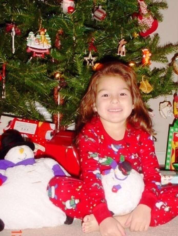 Then: In 2001, 4-year-old, Jordyn Caruso sits in front of the Christmas tree holding the chubby snowmen that were a gift from her grandmother Cindy Mentor. Photo: Courtesy, Caruso, Reader Submission