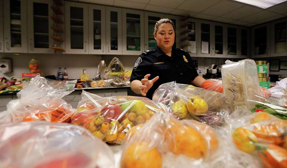 Ginger Herrell-Lopez, a U.S. Customs and Border Protection supervisory agriculture specialist, deals with items confiscated from international travelers at Bush Intercontinental Airport. During the holidays, agents see more prohibited food items. Photo: James Nielsen, Staff / © 2015  Houston Chronicle