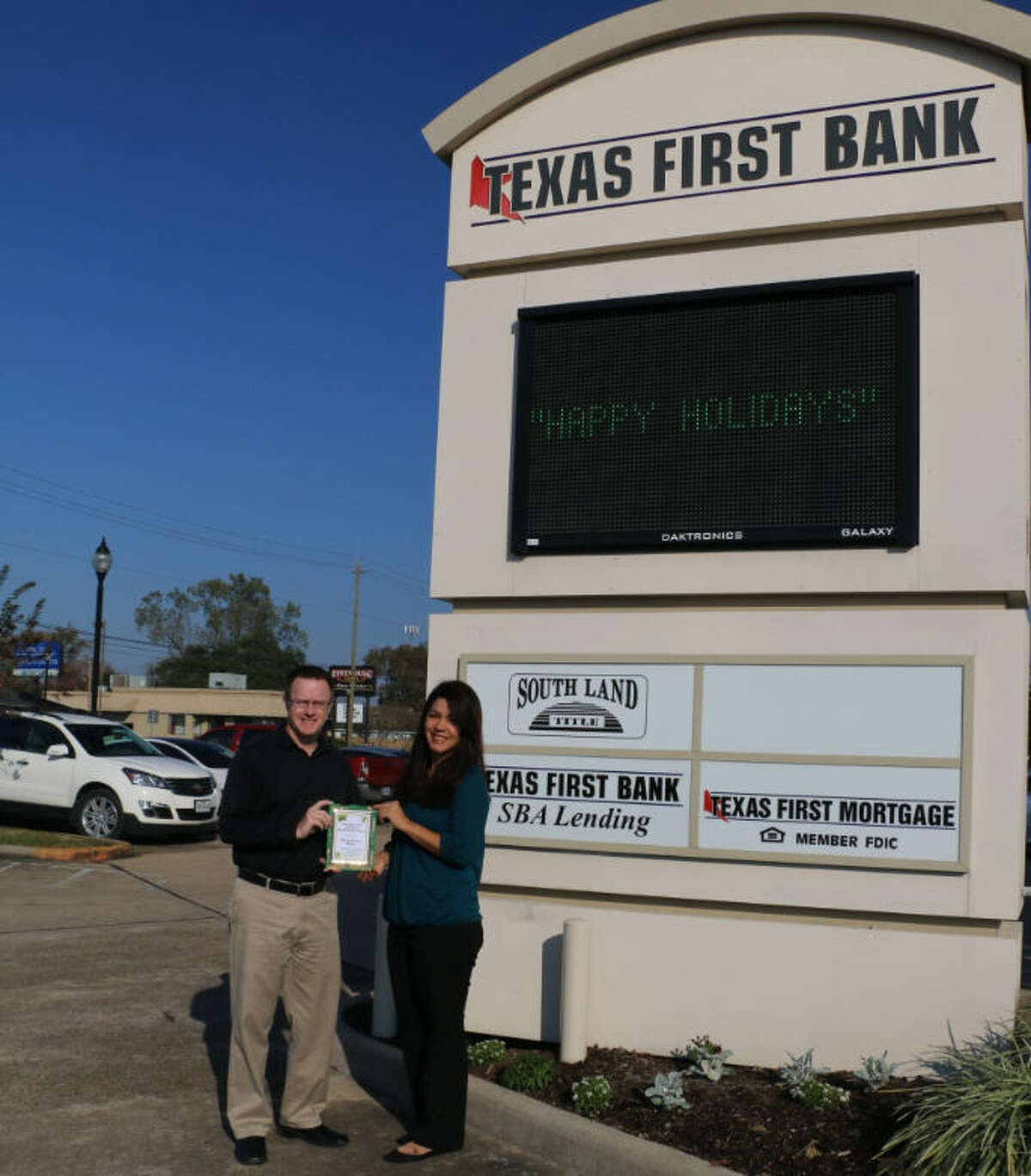 Jason Yowell and Estella Martinez accept the December 2015 Business Beautification Award on the behalf of Texas First Bank.Texas First Bank's parent company will acquire Preferred Bank, expanding its presence in Houston.