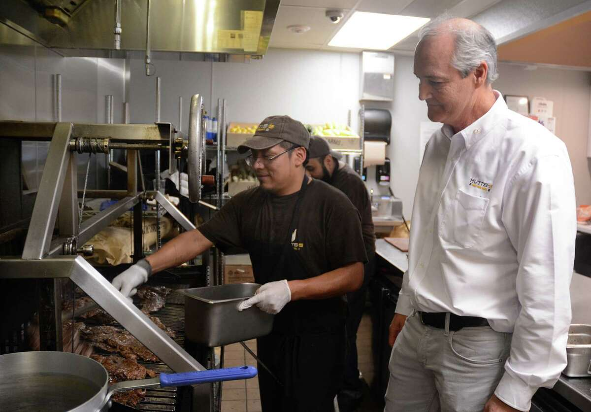 Huti's owner Chris Osborne, of Magnolia, watches as chef Estban Tipaz prepares meat for the lunch crowd in Huti's 5 Free Fire Grill, 2501 Research Forest in The Woodlands. Photograph by David Hopper