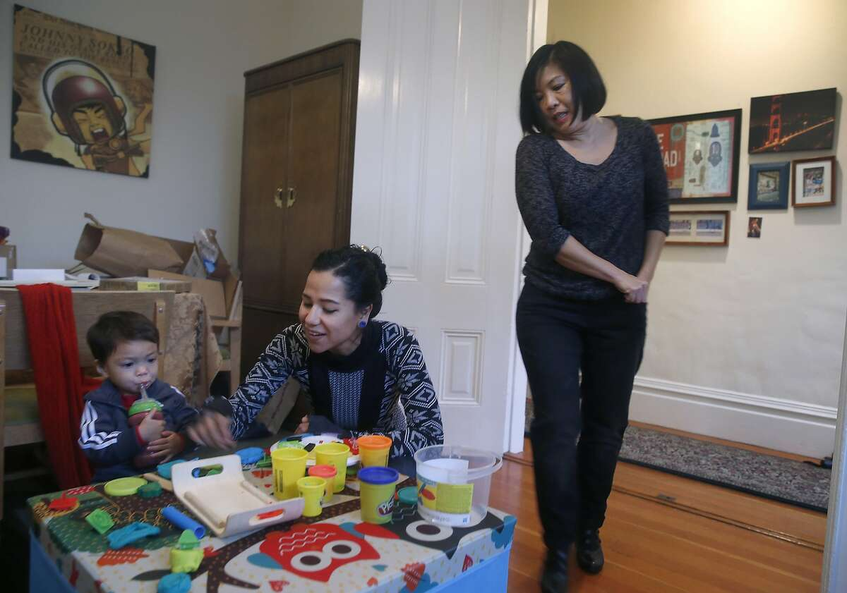 Nanny Zaira Medina (center) plays with 21-month-old Kingston Stillman as his mother Stephanie Ong Stillman prepares to leave for work in San Francisco, Calif. on Tuesday, Dec. 22, 2015. Ong Stillman had an impossible time finding daycare for Kingston just after he was born so Stillman turned to Medina for a shared nanny arrangement with another family.