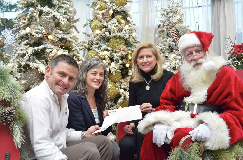 From left, McArdle's owner James McArdle, Katie Kilroy from Kids in Crisis, Tami Ketler of TMK Sports and Entertainment and Santa himself were on hand for the presentation of a $3,300 check to benefit Kids in Crisis. Photo: / Contributed Photo