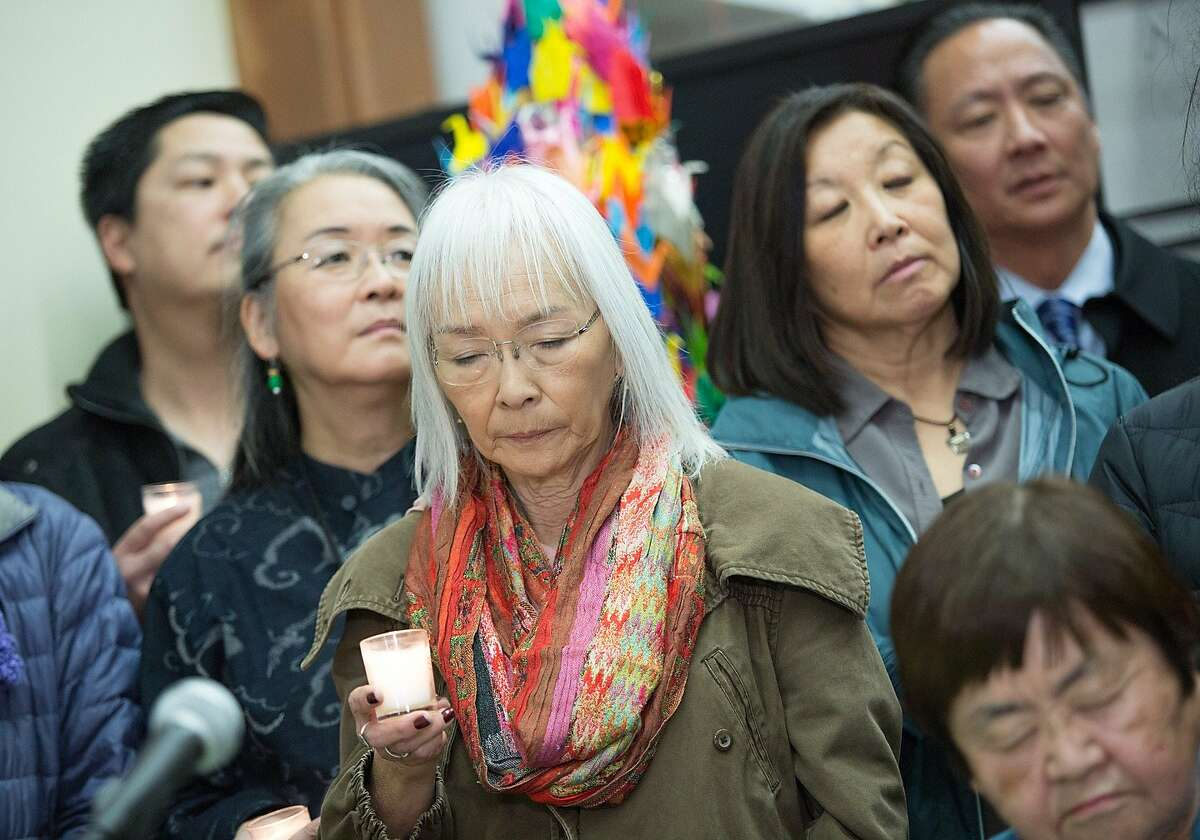 Judy Hamaguchi, center, and community members hold a moment of silence during a news conference at the National Japanese American Historical Society in Japantown, Tuesday, Dec. 22, 2015, in San Francisco, Calif. Hamaguchi is the S.F. Japanese American Citizens League board president. Japanese Americans from the Bay Area Day of Remembrance Consortium expressed support and solidarity with the Muslims, Sikh, Arab and South Asian American communities.