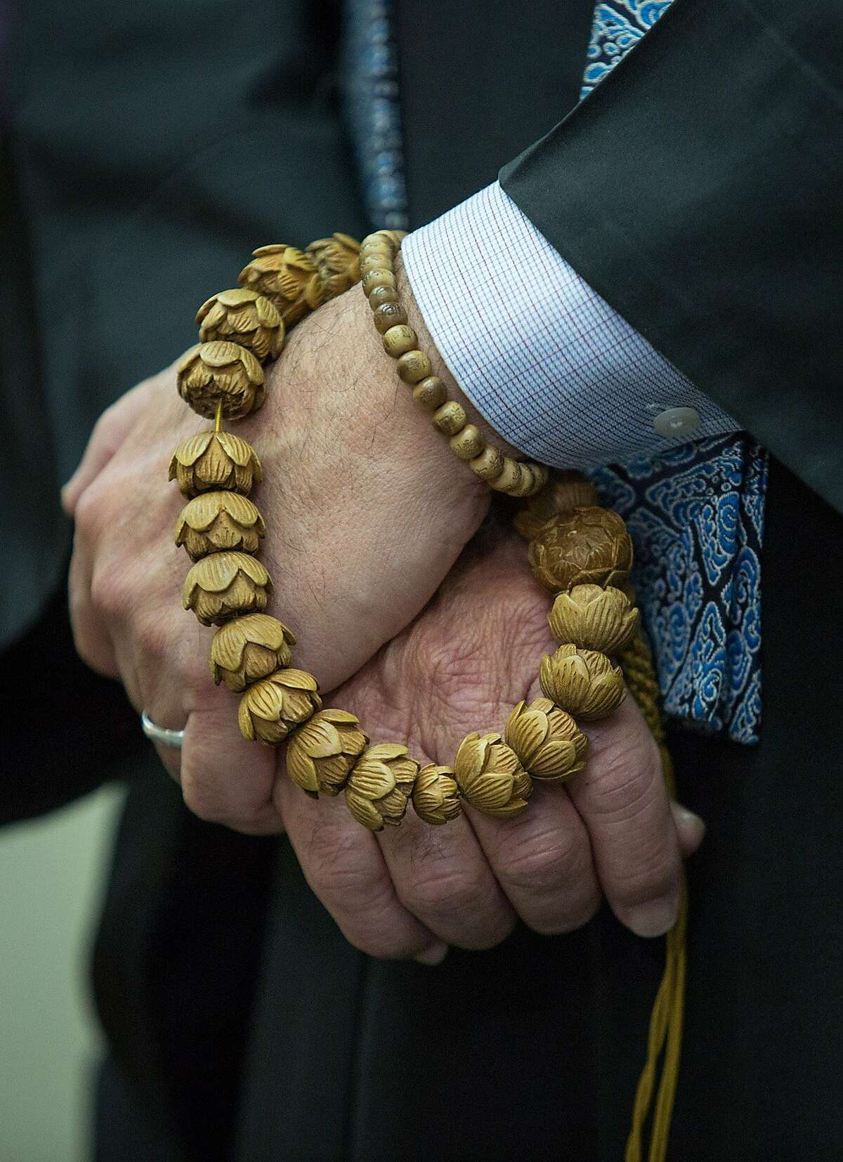 Rev. Ronald K. Kobata of the Buddhist Church of San Francisco holds an onenju, prayer beads, during a moment of silence during a news conference at the National Japanese American Historical Society in Japantown, Tuesday, Dec. 22, 2015, in San Francisco, Calif. Japanese Americans from the Bay Area Day of Remembrance Consortium expressed support and solidarity with the Muslims, Sikh, Arab and South Asian American communities.