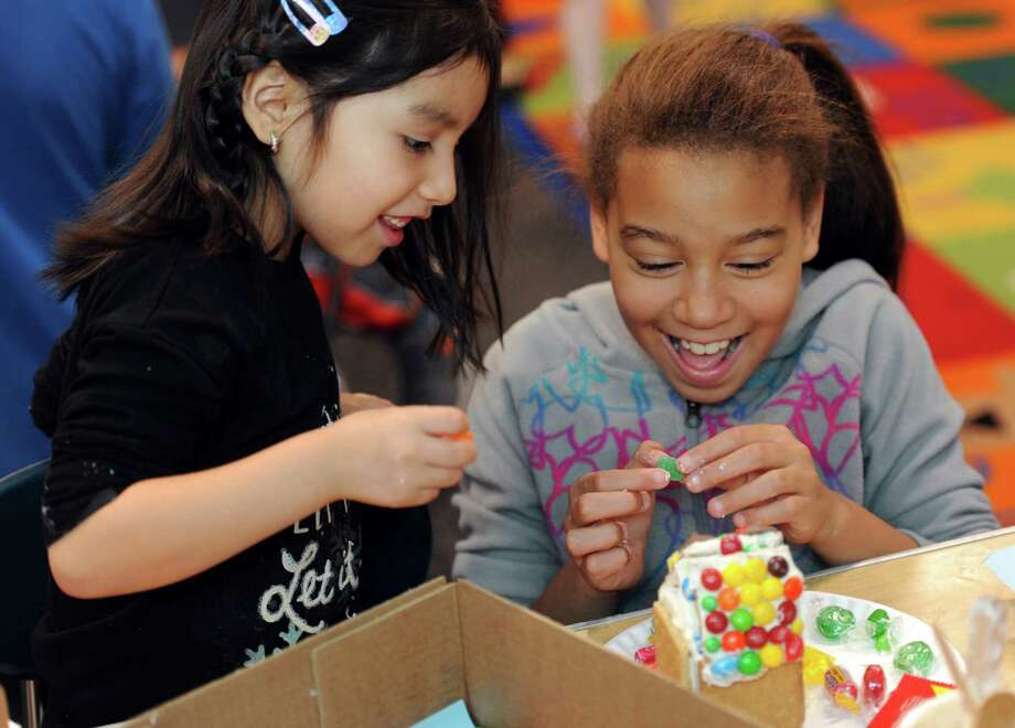 New Lebanon School kindergarten student Kamila Zhunio and fifth-grader Lia Warburton collaborate on the construction of a gingerbread house on Tuesday at the Byram Archibald Neighborhood Center in Greenwich. The gingerbread house built is a New Lebanon tradition where fifth-graders pair up with their younger counterparts to work together to build the candy-covered homes. Photo: Autumn Driscoll / Hearst Connecticut Media / Connecticut Post