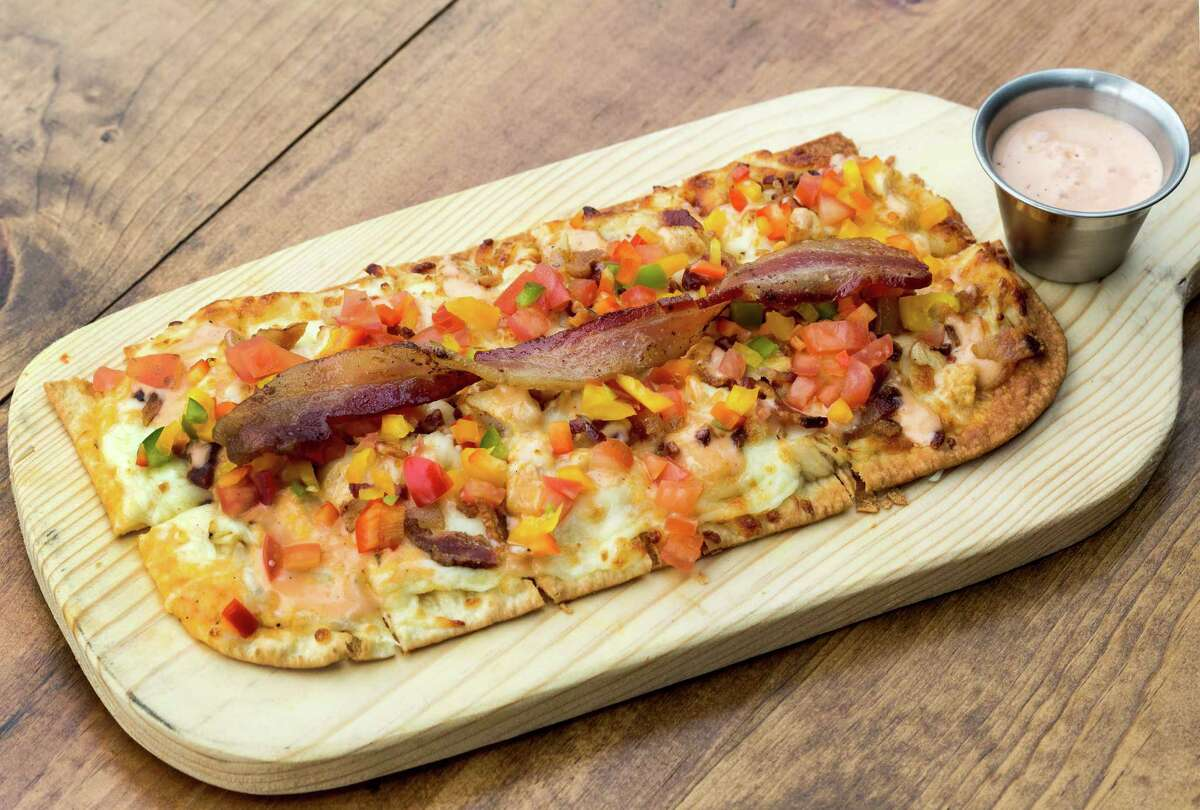 Revolver Bourbon Social has opened at 6502 Washington with an extensive menu of bourbon and whiskey, beer, wine and craft cocktails as well as a Texas-inflected American pub menu. Shown: Chicken Bacon Ranch Flatbread.