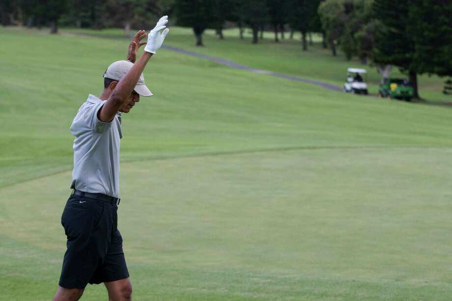 President Barack Obama celebrates after hitting a long chip shot on the 18th hole during a round of golf at Mid-Pacific Country Club, Monday, Dec. 21, 2015, in Kailua, Hawaii. (AP Photo/Evan Vucci) Photo: Evan Vucci, Associated Press / AP