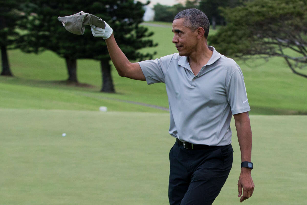President Barack Obama tips his cap to a crowd of onlookers after hitting a long chip shot on the 18th hole during a round of golf at Mid-Pacific Country Club, Monday, Dec. 21, 2015, in Kailua, Hawaii. (AP Photo/Evan Vucci)