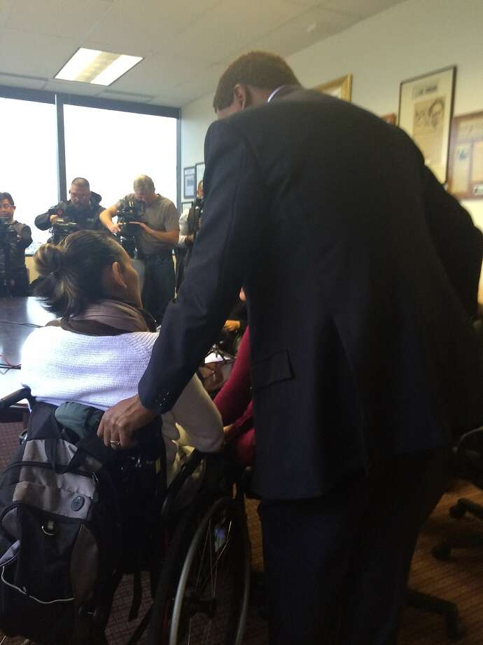 Hung Lam, 36, speaks to the media in his wheel chair at his attorneys' law offices in Oakland.
