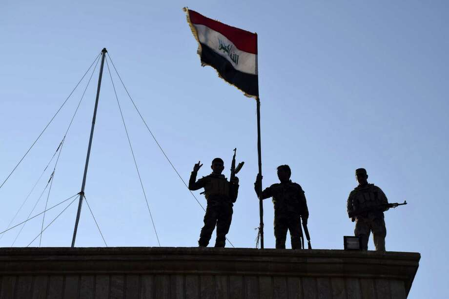 In this Monday, Dec. 21, 2015 photo, Iraqi soldiers plant the national flag over a government building in Ramadi as security forces advance their position in northern Ramadi, 70 miles (115 kilometers) west of Baghdad, Iraq. Iraqi forces on Tuesday reported progress in the military operation to retake the city of Ramadi from the Islamic State group, saying they made the most significant incursion into the city since it fell to the militants in May. (AP Photo) Photo: Uncredited, STR / Associated Press / AP