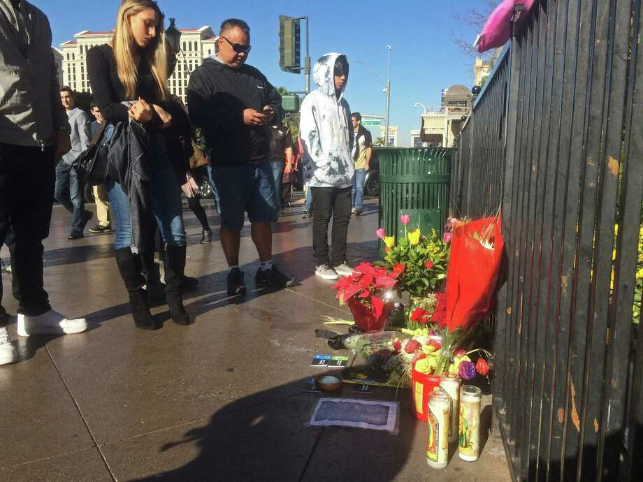 People stop to look at makeshift memorial for crash victims on the strip in Las Vegas on Tuesday, Dec. 22, 2015. A woman accused of intentionally plowing a car carrying her young daughter through crowds of pedestrians on the Las Vegas Strip was charged Tuesday with murder, child abuse and hit-and-run. The crash killed Jessica Valenzuela, 32, of Buckeye, Ariz., and injured at least 35 people. (AP Photo/Brian Skoloff) Photo: Brian Skoloff, STF / AP