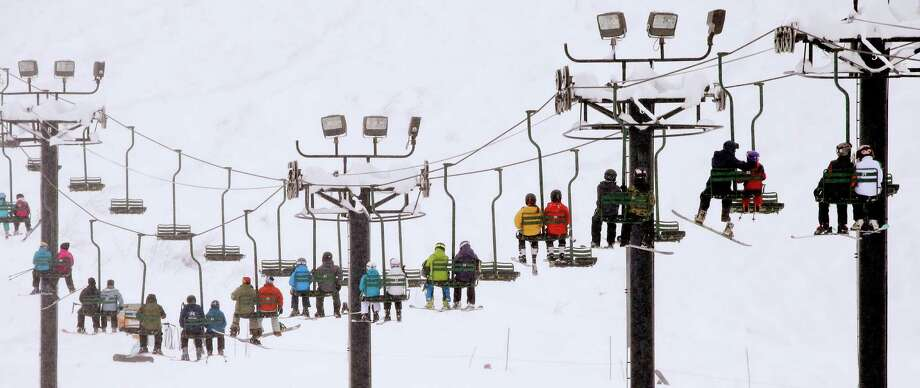 Skiers and snowboarders ride a lift up a mountain on Tuesday, Dec. 22, 2015, at Snoqualmie Pass, Wash. A weather pattern that could be associated with El Nino has turned winter upside-down across the U.S. during a week of heavy holiday travel, bringing spring-like warmth to the Northeast, a risk of tornadoes in the South and so much snow in parts of the West that there are concerns about avalanches. (AP Photo/Elaine Thompson) Photo: Elaine Thompson, STF / Associated Press / AP