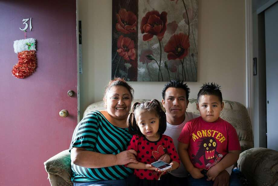 Eloisa Herrera, left, and Jorge Sr. Lopez pose with their children Yaretzi and Jorge Jr. Lopez at their home in Sunnyvale, Calif on Tuesday, Dec. 22, 2015. Herrera had an barren apartment until the Chronicle bought them a king-size bed, bunkbeds and a dining room set. Photo: James Tensuan
