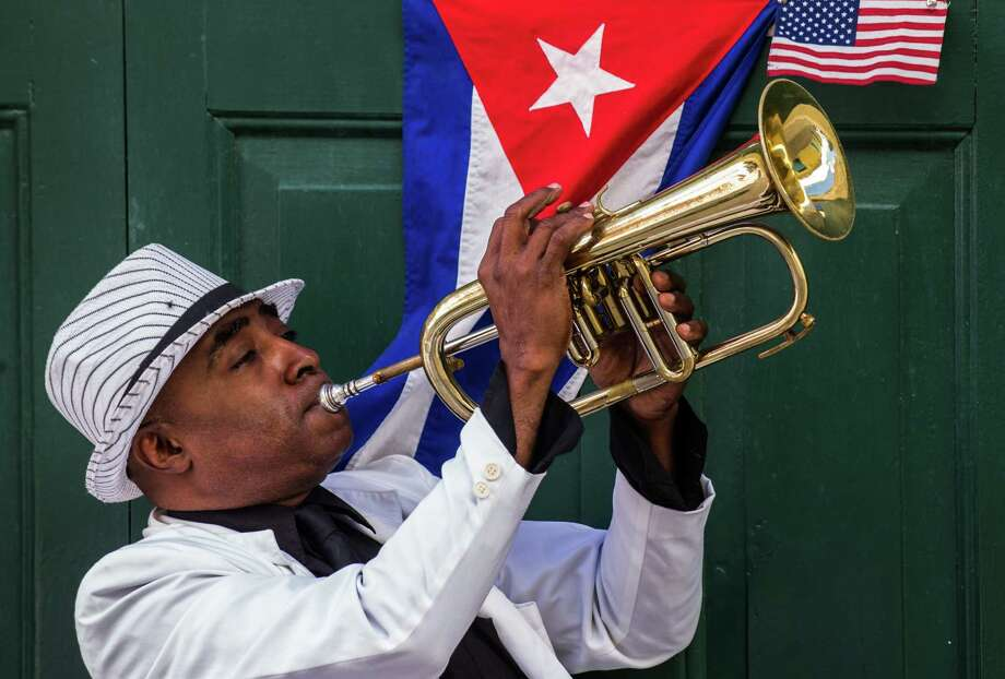 A man plays the trumpet  next to Cuban and U.S. flags in Havana on Dec. 17, 2015. The United States announced the resumption of regular flights to and from Cuba, the latest step in a historic thaw in relations. On Dec. 16, the United States and Cuba reached a bilateral arrangement to establish scheduled air services between the two countries, the State Department said in a statement. (AFP/Getty Images) Photo: YAMIL LAGE, Stringer / AFP