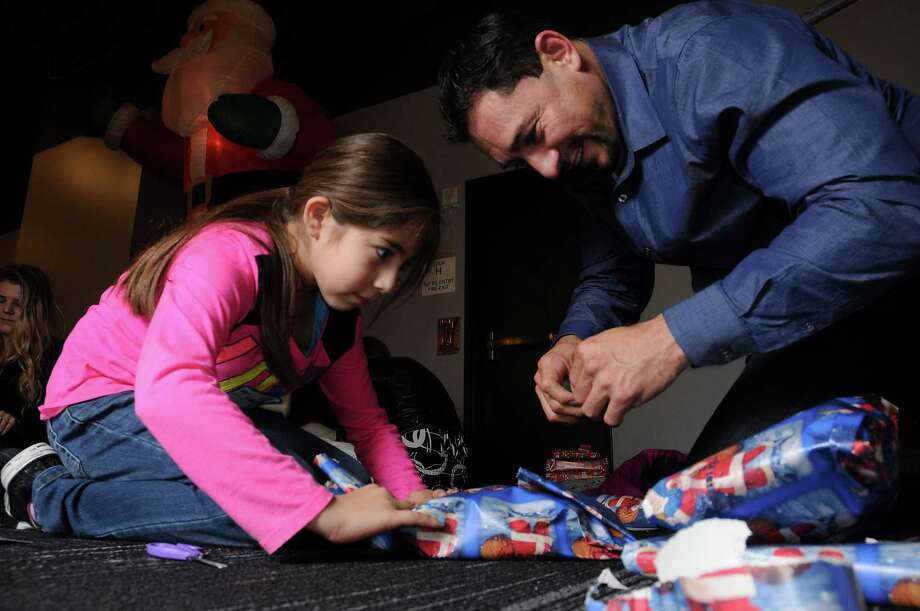 Paul Humerez and his daughter Isabella, 8, helped wrap Christmas gifts for area families at Lakewood Church last week. Photo: Dave Rossman, Freelance / Freelalnce