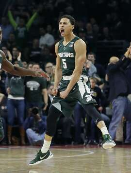Michigan State guard Bryn Forbes celebrates a three-point basket during overtime of an NCAA college basketball game against Oakland, Tuesday, Dec. 22, 2015, in Auburn Hills, Mich. Michigan State defeated Oakland 99-93. (AP Photo/Carlos Osorio)