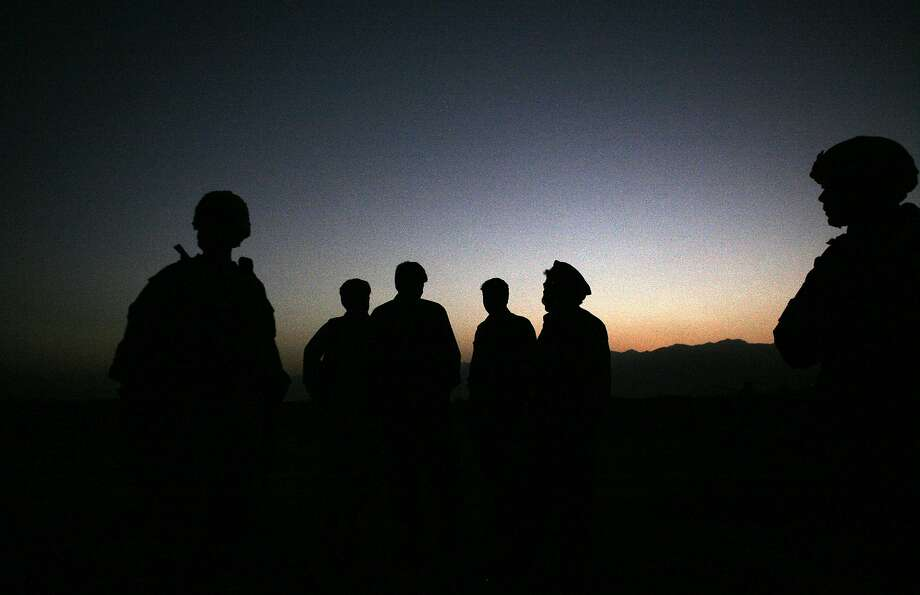 In this Sunday, Oct. 18, 2009 file photo, U.S. Army soldiers stand with Afghan policemen before a joint patrol of Qalanderkhail, outside of Bagram Air Field in Afghanistan. Photo: Maya Alleruzzo, Associated Press