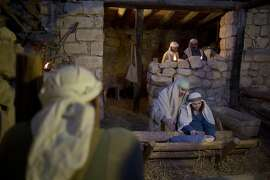Christian actors play the parts of Joseph and Mary during a re-enactment of a Nativity scene of the birth of Jesus Christ as part of Christmas festivities at the Nazareth Village in the northern Israeli city of Nazareth, Tuesday, Dec. 22, 2015. (AP Photo/Ariel Schalit)