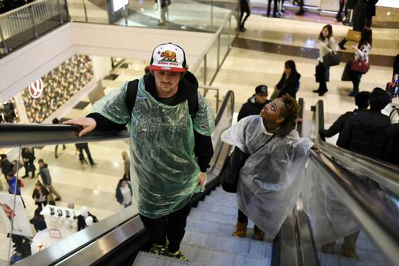 Homeless youth Chase McNamara, 22, and Alexis Jefferson, 18, ride an escalator at the Westfield Mall as they try to dry off after asking for spare change in the rain, in San Francisco, CA Monday, December 21, 2015.