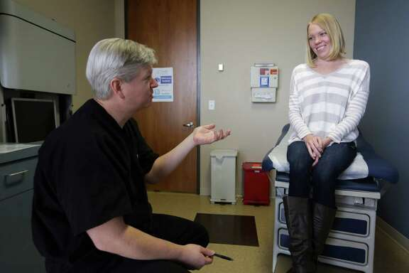 Director of elective general surgery at The University of Texas Health Science Center at Houston (UTHealth) and medical director of bariatric surgery at Memorial Hermann-Texas Medical Center Erik Wilson, left, has a follow-up appointment with Katie Houston after she underwent a recent surgery to fix her acid reflux issue Wednesday, Dec. 2, 2015, in Houston. Houston's acid reflux was so bad she used to throw up everything she ate. ( Michael Ciaglo / Houston Chronicle )
