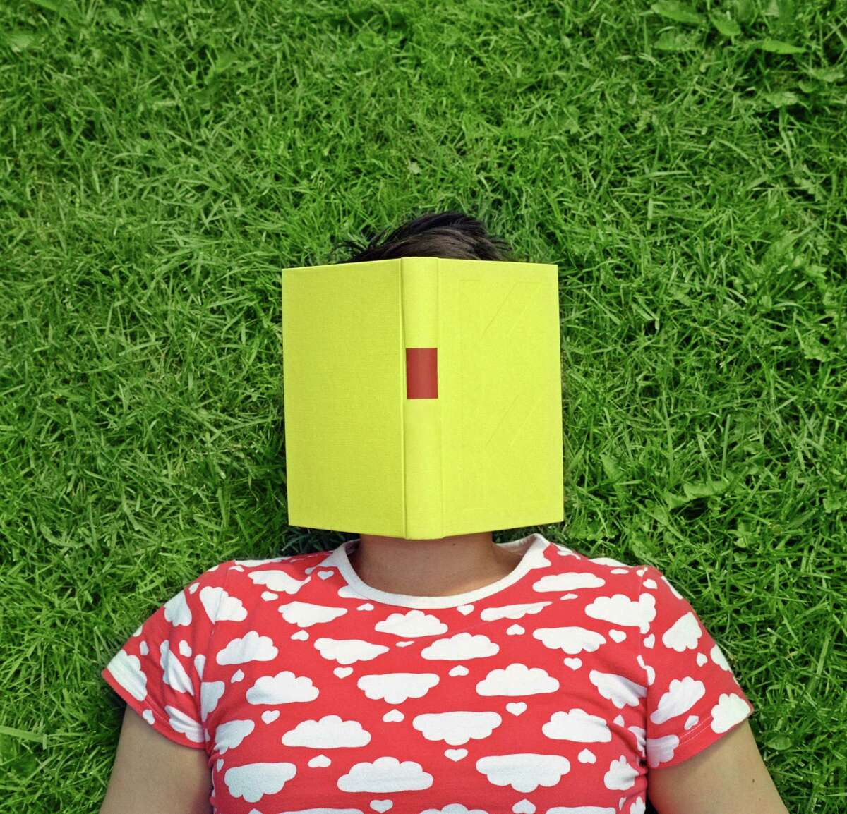 Mid adult woman lying on the grass with a book on her face