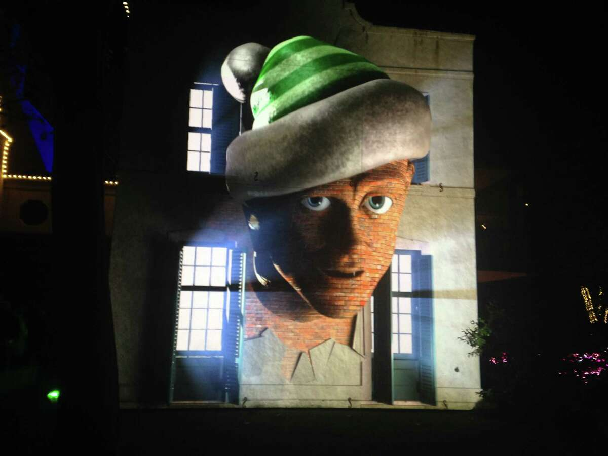 """Miscreant elves appear to pop out of the house in a 3-D-mapped projection that's part of the new """"Christmas Village at Bayou Bend"""" attraction."""