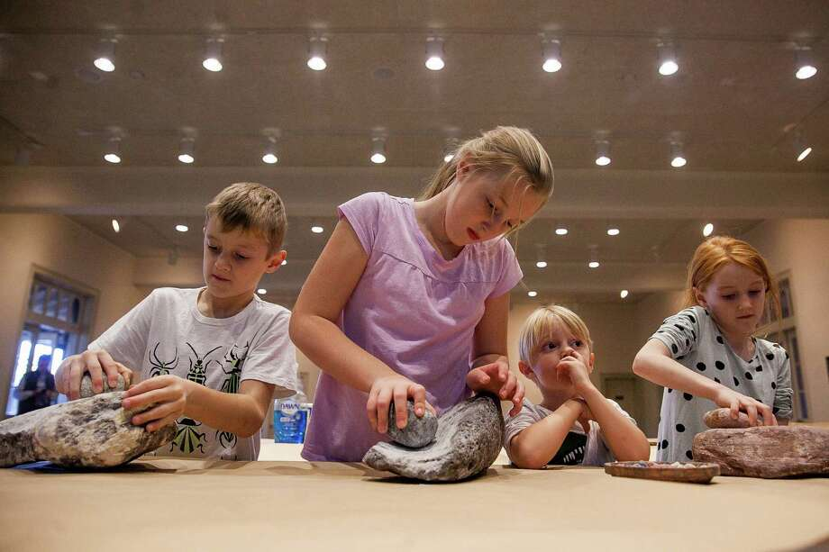 (From left) Siblings Sawyer Fry, 7, Paton, 9, Asher, 3, and Sage, 7, crush minerals into a powder that will be used as paint pigment during a rock art activity Tuesday Dec. 8, 2015 at the Witte Museum. Photo: Julysa Sosa/ For The San Antonio