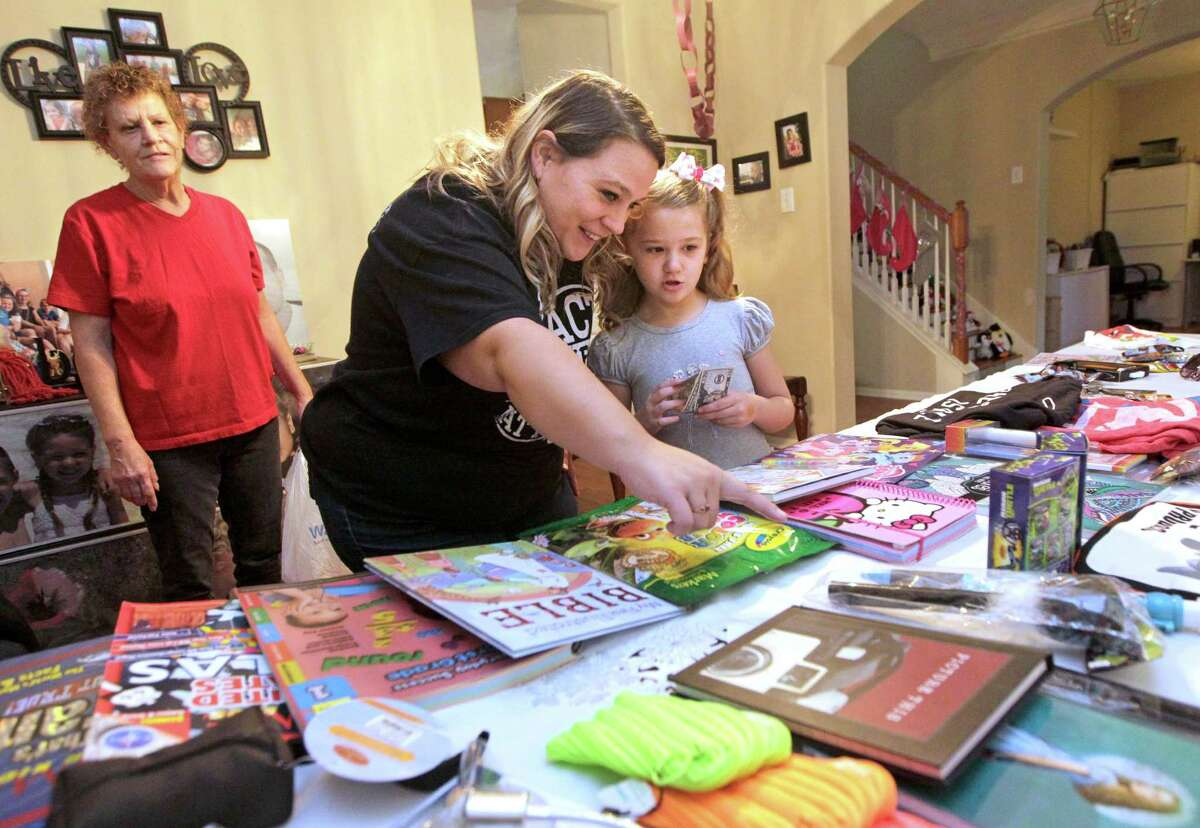 """Heather Feagain helps her daughter, LilyKate, 8, pick items to buy as Christmas presents, as aunt Joanne Dumire looks on, in Sugar Land. Items are purchased with Monopoly-like """"mama bucks"""" that the children earn for performing chores."""