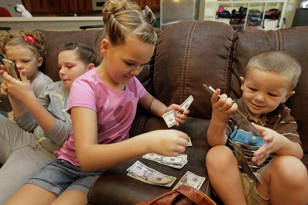 """Siblings Annelise Feagain, 7, left, Eva Feagain, 11, Grace Feagain, 10, and Leo Feagain, 4, prepare to spend their """"mama bucks"""" on Christmas presents at their Sugar Land home."""