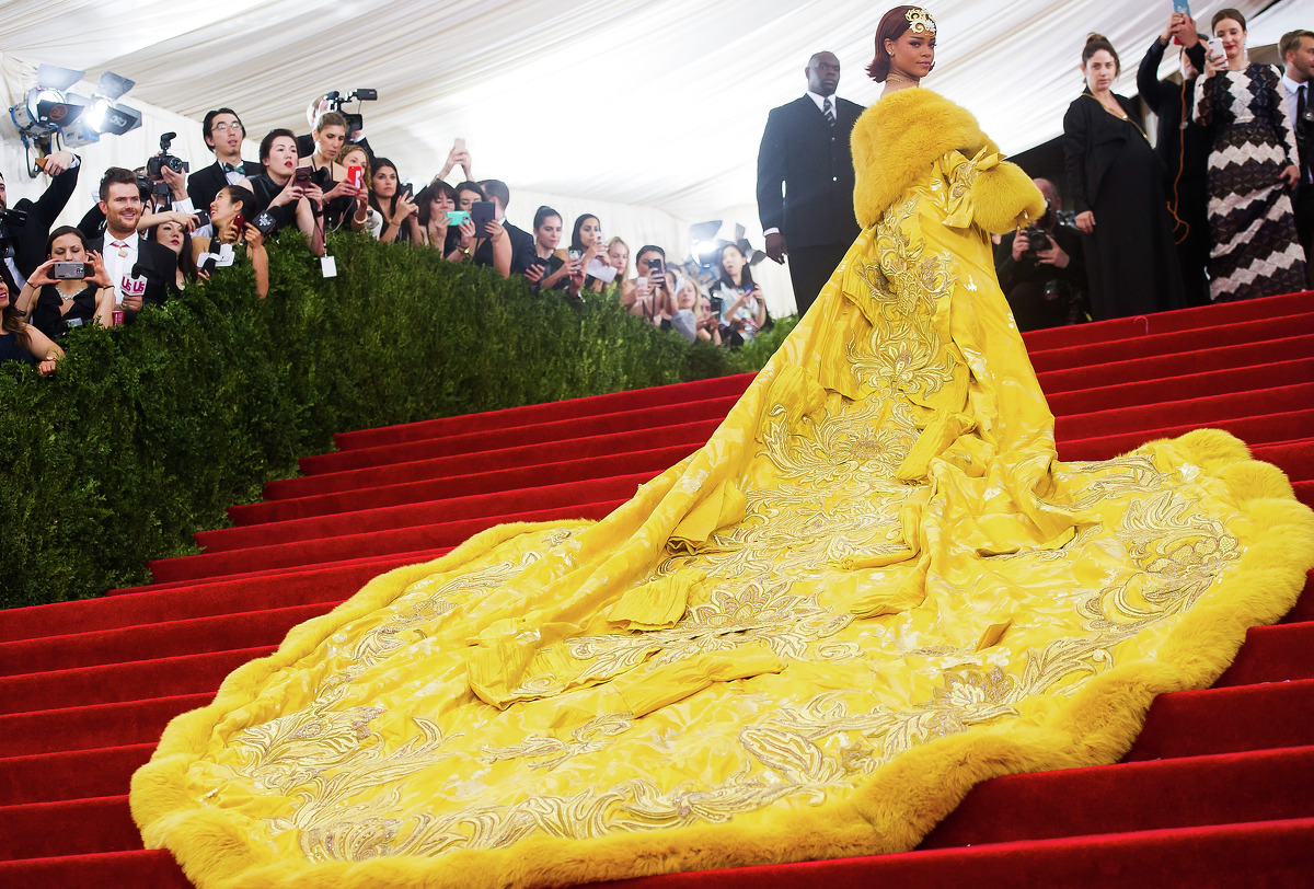 Rihanna arrived in dramatic fashion at The Metropolitan Museum of Art's Costume Institute with a train so long that it required the hellp of three men.