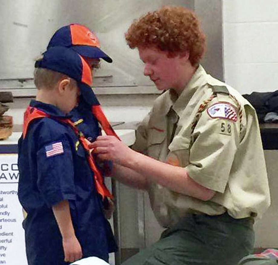New Milford Boy Scout Dylan Lewis of Troop 58, right, was recently honored for his role as den chief, an official youth leadership position of the Boy Scouts of America. Above, Dylan presents Tiger Cub Scouts Andrew Karaffa and Oliver Brandel some awards. Photo: Courtesy Of Jessica Higgins / The News-Times Contributed